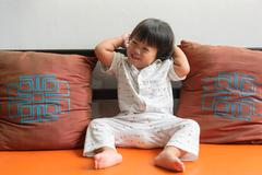 beautiful pretty little girl with happy smile sitting on the sofa - stock photo
