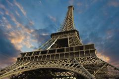 Eiffel Tower at Sunset against a Cloudy Sky Stock Photos
