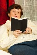 Senior woman reading book home Stock Photos