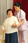 Nurse helping sick senior home Stock Photos