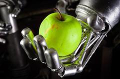 A robot hand holding a fresh apple Stock Photos