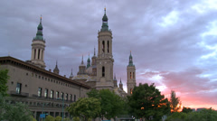 Moving pink clouds over baroque religious monument at sunset Stock Footage