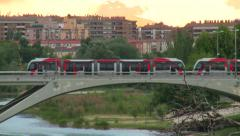 Two tramways meet over the bridge with background sunset sky Stock Footage