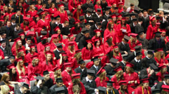 Pan up of graduates as they stand and get ready to graduate. - stock footage