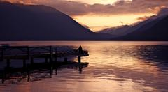 seating on the lake dock during sunset. cloudy hills. lake crescent, washingt - stock photo
