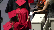 Stock Video Footage of Graduates handing name cards to reader.