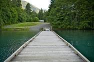 Stock Photo of wood boat dock on lake crescent, washington state, usa. dark green super clea
