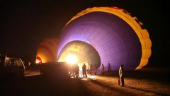 Preparing hot-air balloons for flight at night in Luxor, Egypt Stock Footage