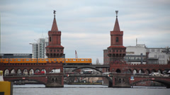 Berlin Landmark -Famous Oberbaum Bridge with the yellow train passing over it Stock Footage