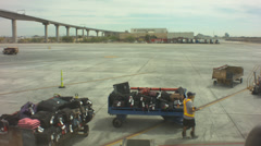 Man pulling baggage cart at airport Stock Footage