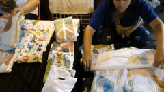 Stalls selling printed t-shirts & guitars at night bazaar, Chiang Mai, Thailand Stock Footage
