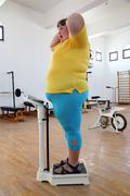 Impressed overweight woman on scales in gym Stock Photos