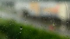 rain - water drops on the window(glass). City in background (blurred shot) - stock footage