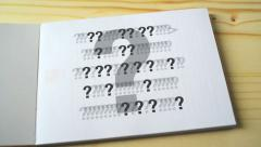 Question marks on the notebook page. Stock Footage
