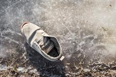 Worn sports shoe frozen puddle Stock Photos