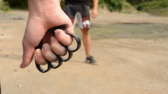 Man threatens man with knuckle-duster - outdoors Stock Footage