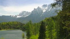 Camera pan from picturesque lake in mountains of the alps. Stock Footage