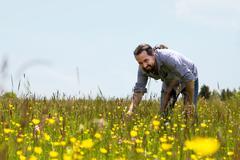 Happy bearded man on a wonderfull flower meadow Stock Photos