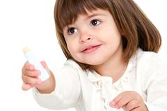 Portrait of little girl with lip balm. - stock photo