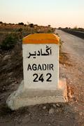 Sign road with distance to agadir Stock Photos