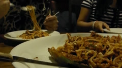 Diners enjoying plates of seafood Spaghetti in a dim-lighted restaurant. Stock Footage