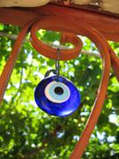 Evil eye talisman or amulet hanging on a garden fence Stock Photos