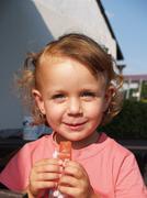 Little girl eating ice lolly - stock photo