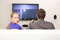 Man watching tv woman looking back Stock Photos