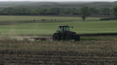 Tractor going by in field pulling plow Stock Footage