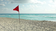 Windy beach weather with red warning flag out Stock Footage