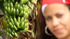 Cuban biracial woman Smiling to camera, banana bunch in background Stock Footage