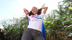 Low angle shot of young biracial Cuban woman dancing with Cuban flag to camera Stock Footage