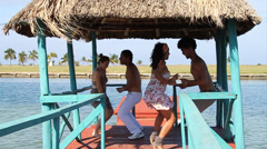Two couples dancing salsa in tiki on pier, silhouette Stock Footage