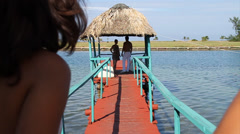Two young couples meet on Tiki Hut on pier over water Stock Footage