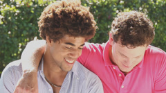 Two young men of mix race laughing hysterical arm around the other Stock Footage