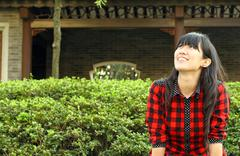 Chinese girl smiling in a garden - stock photo
