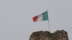 Italian waving flag on top of an ancient tower. Stock Footage