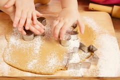 little girls cutting  gingerbread christmas cookies, hands only - stock photo
