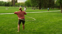 Woman girl hula hooping in busy active park full of people enjoying summer day Stock Footage