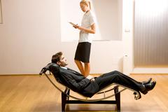 woman reading man lying on chaise longue - stock photo