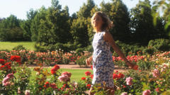 SLO MO MS PAN Happy young woman walking through summer garden, Lehi, Utah, USA Stock Footage