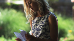 SLO MO MS TU Young woman reading letter in summer garden, Lehi, Utah, USA Stock Footage