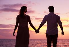 couple watching tropical sunset - stock photo