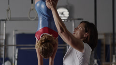 MS TD TU Female instructor assisting girl (8-9) exercising on balance bar in Stock Footage
