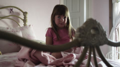 MS Girl (2-3) sitting on bed and dressing up, American Fork, Utah, USA Stock Footage