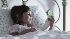 MS Girl (2-3) lying in bed, playing with thermometer, American Fork, Utah, USA Stock Footage