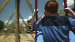 MS Girl (2-3) and boy (10-11) on tire swing in park, American Fork, Utah, USA Stock Footage