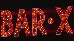 "MS ""Bar X"" neon sign illuminated at night - stock footage"
