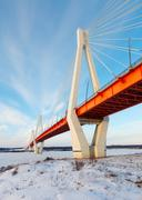 cable-stayed bridge across frosty river - stock photo