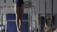 MS TD TU Female instructor assisting girl (10-11) exercising on balance beam, - stock footage